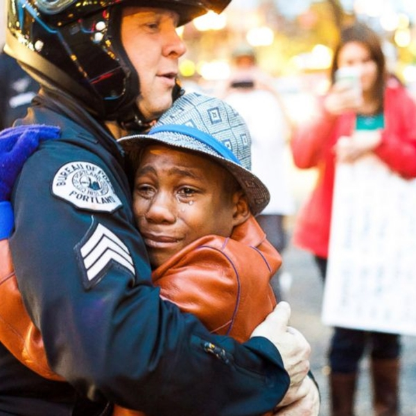"""In a photo shared over 150,000 times on Facebook, 12-year-old Devonte Hart, who was previously holding a sign stating """"Free Hugs,"""" is seen embracing Portland, Oregon, police Sgt. Bret Barnum on Nov. 25, 2014. (Credit: Johnny Nguyen/ http://www.chambersvisuals.com )"""