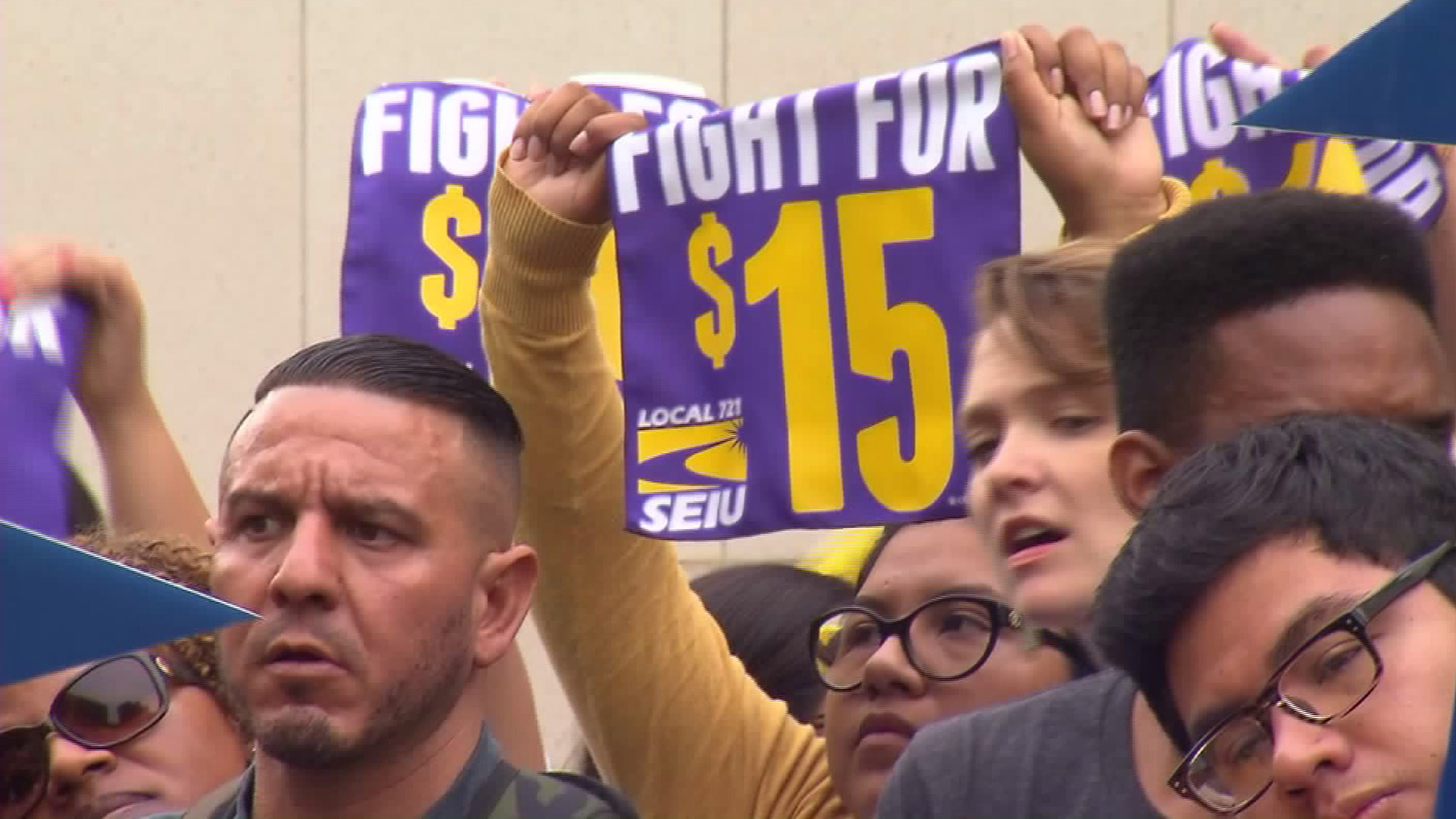 Supporters of the minimum wage hike rally outside the Hall of Administration on July 21, 2015. (Credit: KTLA)