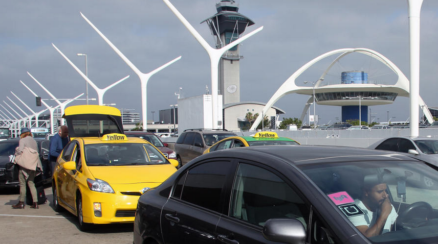 A driver with Uber and Lyft stickers on a car's windshield is seen at LAX's departures level in July 2015. (Credit: Irfan Khan / Los Angeles Times)