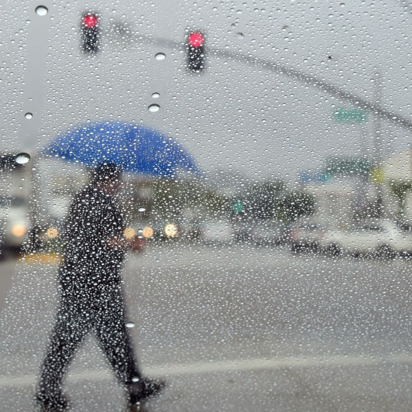 A man crosses a street during a steady rainfall on Sept. 15, 2015, in Los Angeles. (Credit: FREDERIC J. BROWN/AFP/Getty Images)