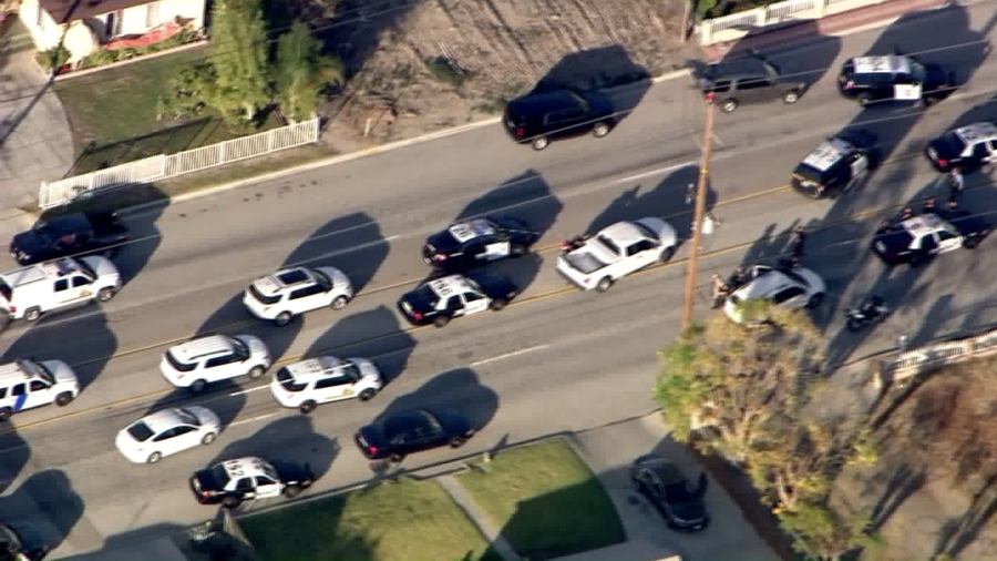 Authorities swarmed an area where a heavily damaged black SUV was stopped following a mass shooting in San Bernardino on Dec. 2, 2015. (Credit: KTLA)