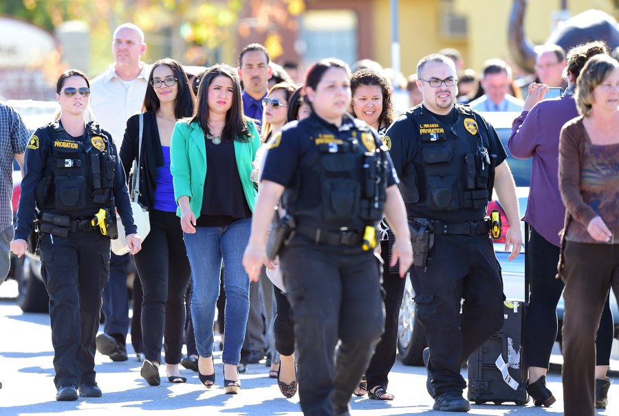 Police escort civilians away from the 1300 block of S. Waterman Street near the site of a mass shooting that took place on Dec. 2, 2015, in San Bernardino, California. (Credit: Frederic J. Brown/AFP/Getty Images)