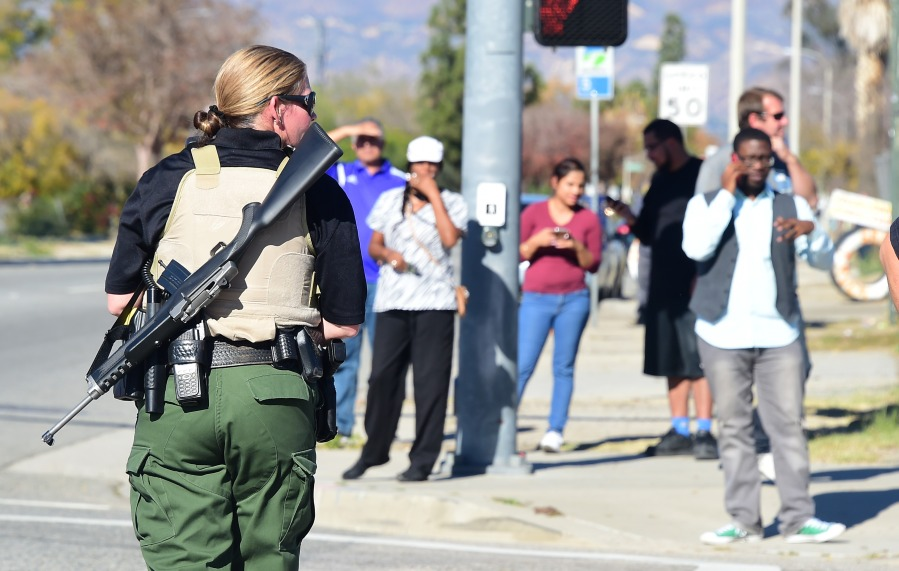 A heavily armed officer sets up a perimeter near the site of a shooting that took place on Dec. 2, 2015, in San Bernardino, California. (Credit: Frederic J. Brown/AFP/Getty Images)