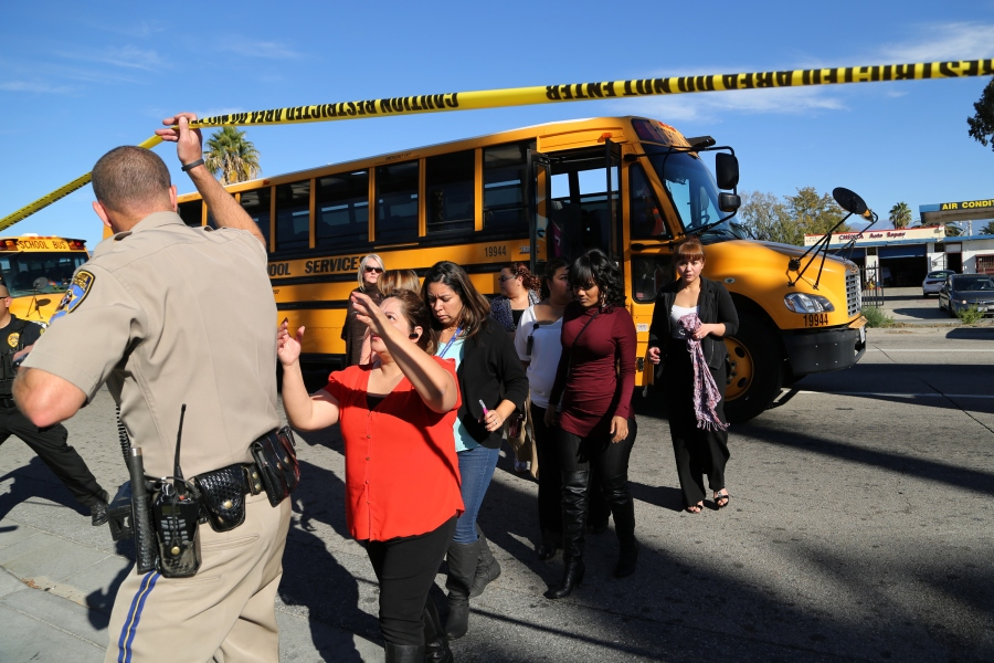 Employees and others people are evacuated by bus from the site of a mass shooting at the Inland Regional Center on Dec. 2, 2015, in San Bernardino, California. (Photo by David McNew/Getty Images)