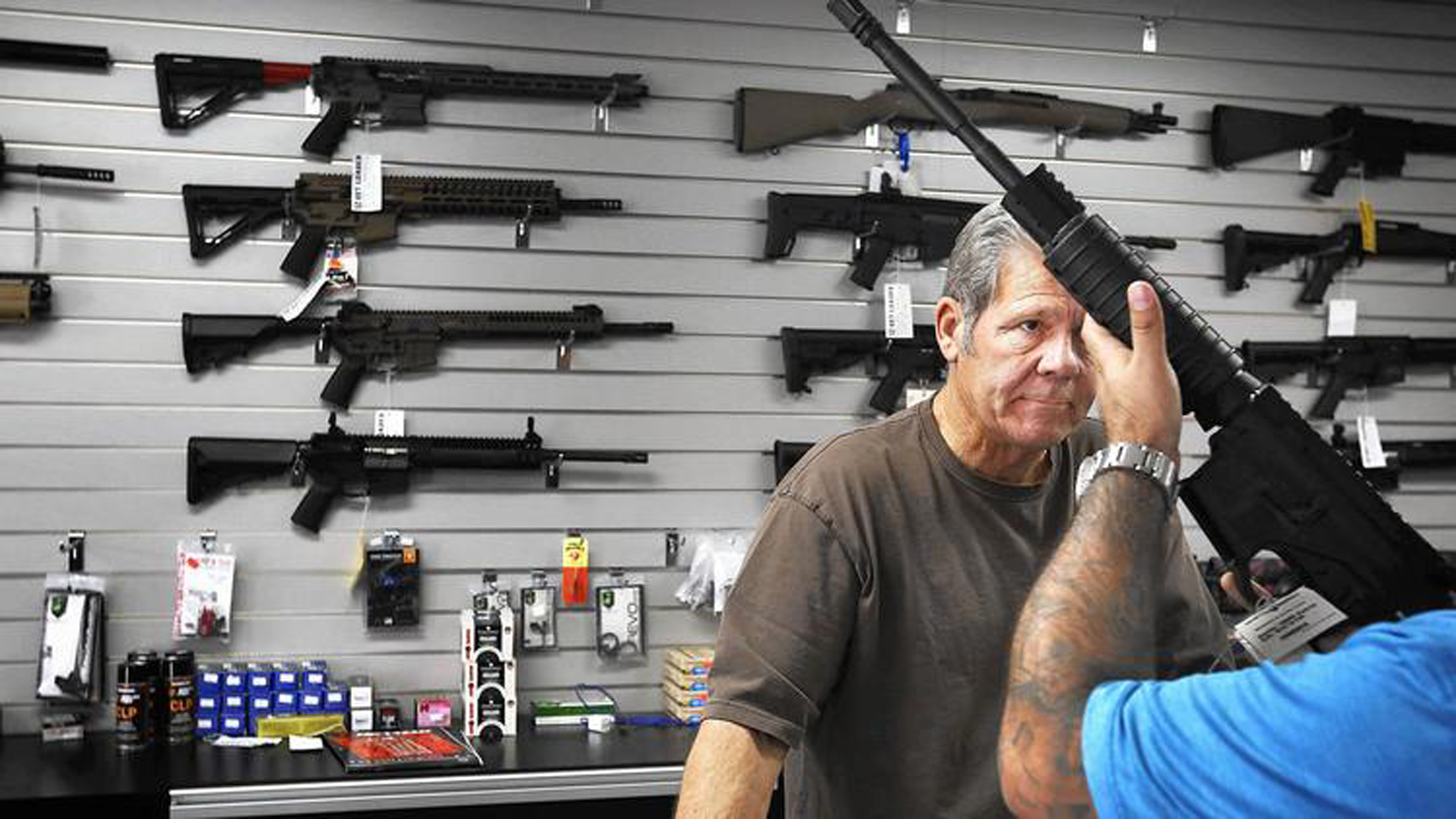Frank Cobet of Get Loaded in Grand Terrace shows a customer a AR-15 rifle. store in Grand Terrace in 2015. (Credit: Barbara Davidson / Los Angeles Times)