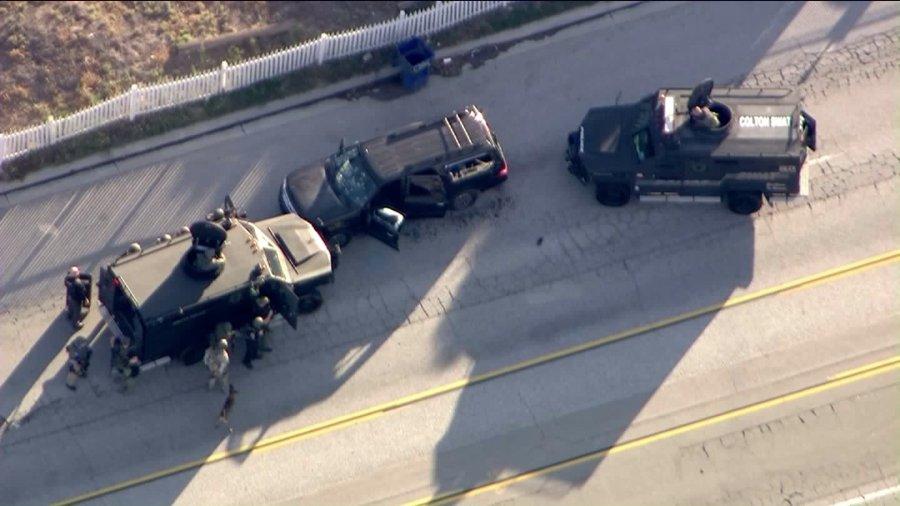 Authorities surround a heavily damaged SUV in San Bernardino on Dec. 2, 2015. (Credit: KTLA)