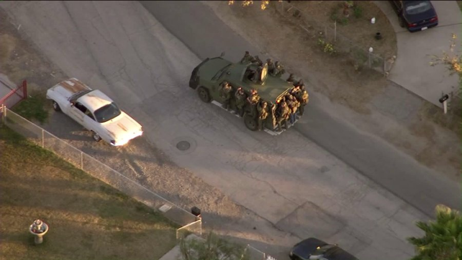Authorities are seen in the area where homes were being surrounded following a mass shooting in San Bernardino on Dec. 2, 2015. (Credit: KTLA)