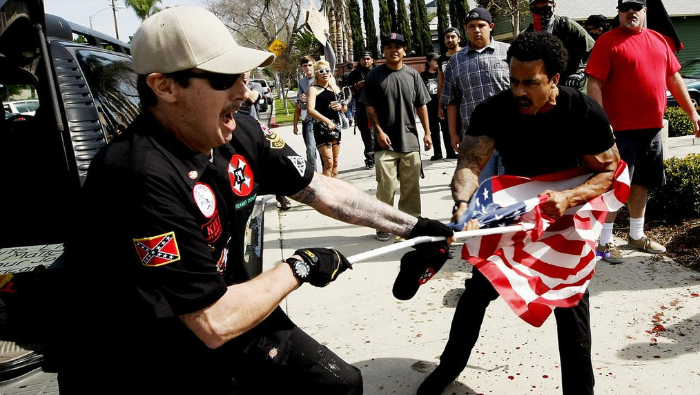 """A Ku Klux Klansman, left, struggles with a protester for an American flag after members of the KKK tried to start a """"White Lives Matter"""" rally at Pearson Park in Anaheim on Feb. 27, 2016. Three people were treated at the scene for stab wounds, and 13 people were arrested. (Credit: Luis Sinco / Los Angeles Times)"""