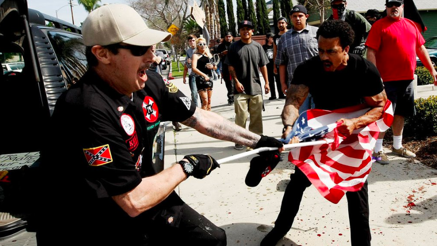 "A Ku Klux Klansman, left, struggles with a protester for an American flag after members of the KKK tried to start a ""White Lives Matter"" rally at Pearson Park in Anaheim on Feb. 27, 2016. Three people were treated at the scene for stab wounds, and 13 people were arrested. (Credit: Luis Sinco / Los Angeles Times)"