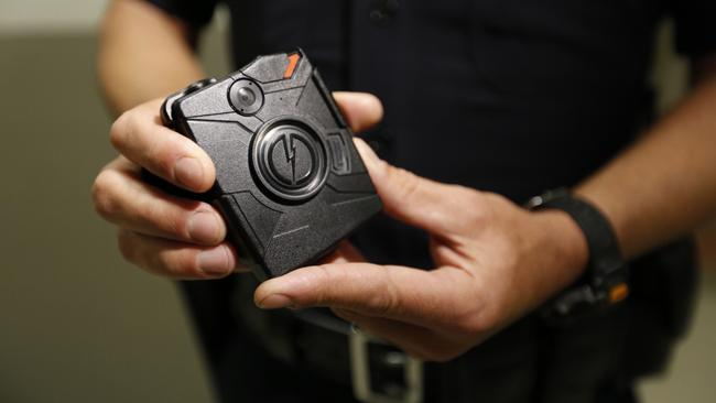A Los Angeles police officer demonstrates how body cameras work in August 2015. Cameras in four LAPD divisions captured nearly 255,000 videos between August and December 2015, according to a new report from the department. (Credit: Al Seib / Los Angeles Times)