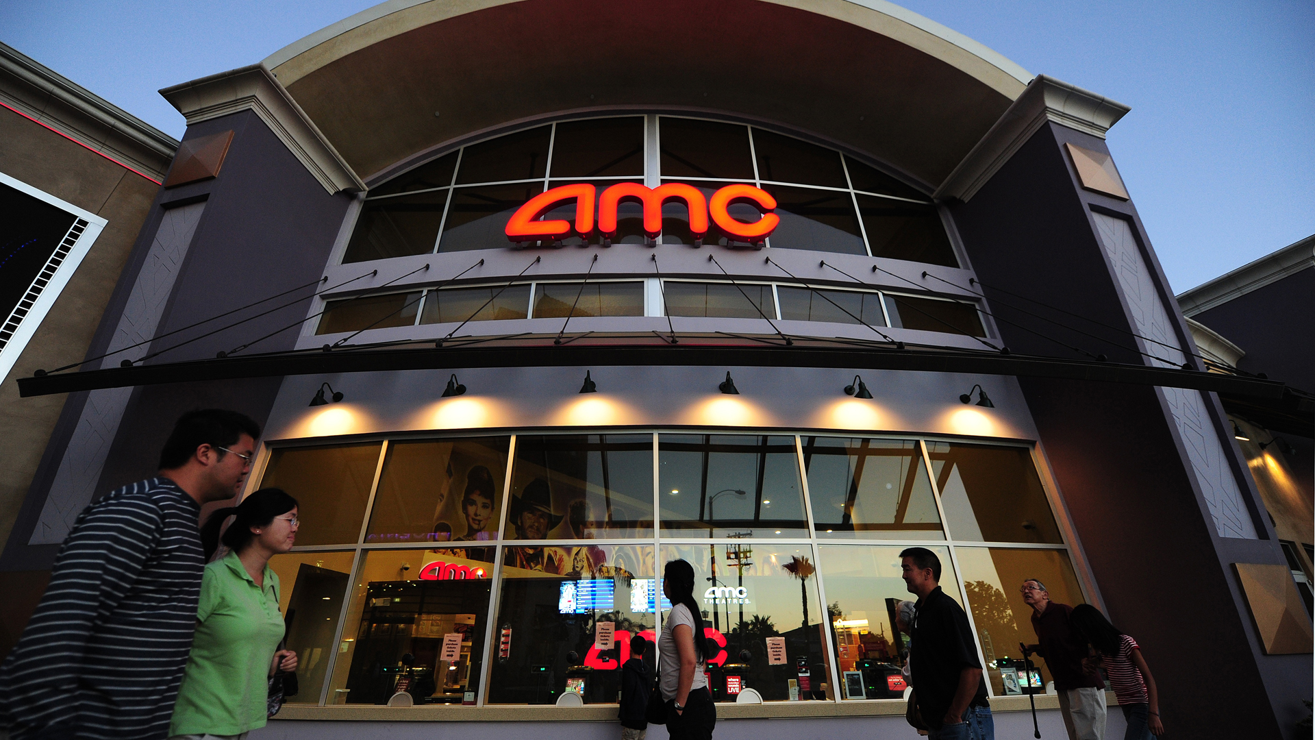 People walk past movie theaters of the US cinema chain AMC Entertainment in Monterey Park on May 22, 2012. (Credit: FREDERIC J.BROWN/AFP/GettyImages)