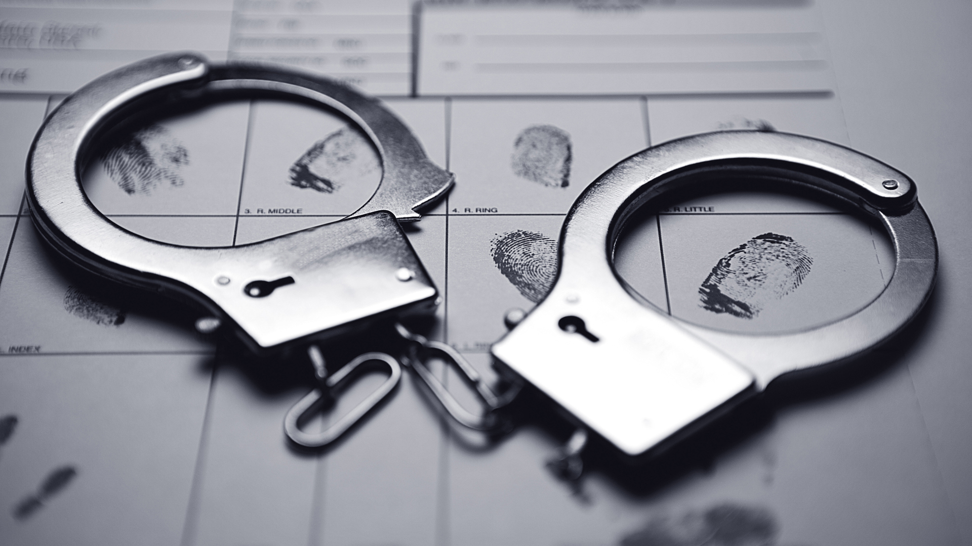 Handcuffs on top of a fingerprint form are shown in this file photo. (Credit: Blake David Taylor/Thinkstock)