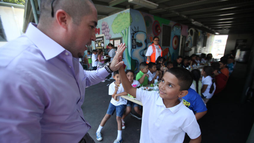 Juan Carlos Rodriguez, left, Title I coordinator, gives a high-five to second-grader Armando Rodriguez, 7, during lunch on the first day of school at Hadden Elementary School in Pacoima in August 2013. (Los Angeles Times)