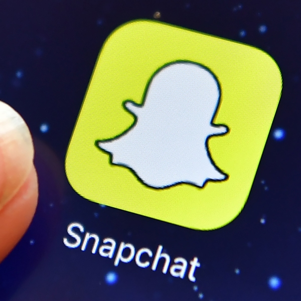 A finger is posed next to the Snapchat app logo on an iPad on Aug. 3, 2016 in London, England. (Credit: Carl Court/Getty Images)