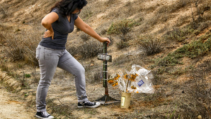 Michelle Glenn offers prayers at a make-shift memorial in front of the home where her cousin, Miguel Ferreyra, and four other adults died in suspicious fire that gutted a care facility at 41400 block of Cruz Way, Temecula, on Aug. 29, 2016. (Credit: Irfan Khan / Los Angeles Times)