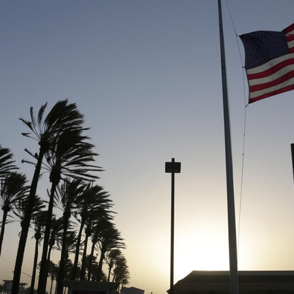 In this file photo, palm trees sway and a flag flutters in gusty winds in Fontana as Santa Ana winds move into Southern California. (Credit: Irfan Khan / Los Angeles Times)