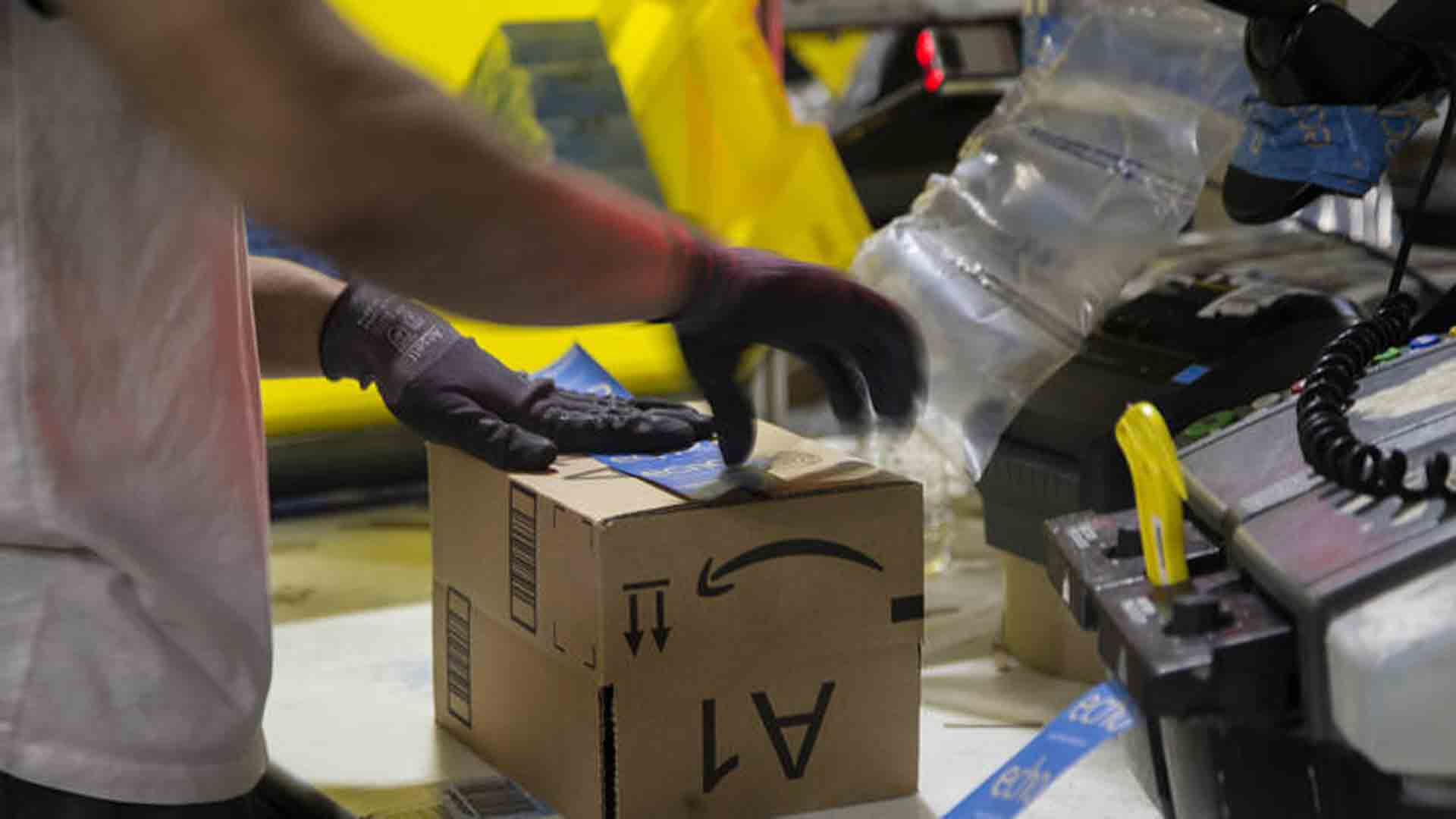 A worker tapes a box while packing items on Cyber Monday at the Amazon Fulfillment Center in San Bernardino. (Credit: Gina Ferazzi / Los Angeles Times)