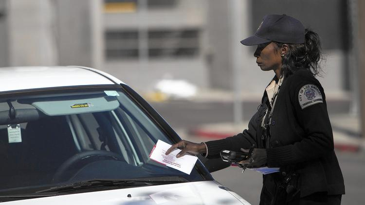 A parking enforcement officer tickets a car parked in an area scheduled for street sweeping in an undated photo. (Gina Ferazzi / Los Angeles Times)