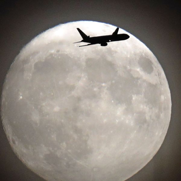 A commercial jet flies in front of the moon on its approach to Heathrow airport in west London on November 13, 2016. (Credit: ADRIAN DENNIS/AFP/Getty Images)