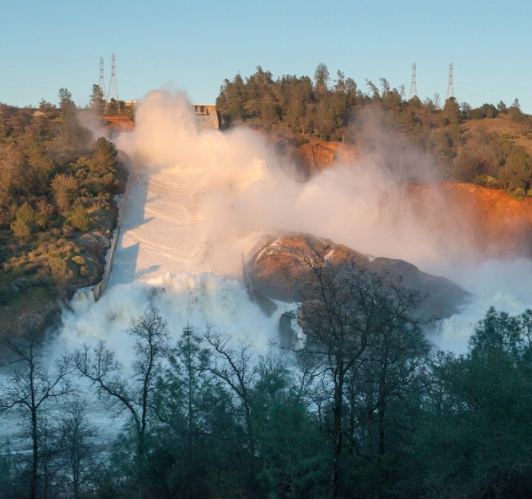 The heavy flows from the 3,000-foot main Oroville dam spillway continues to push debris into the turbid Feather River as the concrete span further eroded and the jagged fracture in its midsection sends water flowing over an adjacent hillside. (Credit: Florence Low / California Department of Water Resources)