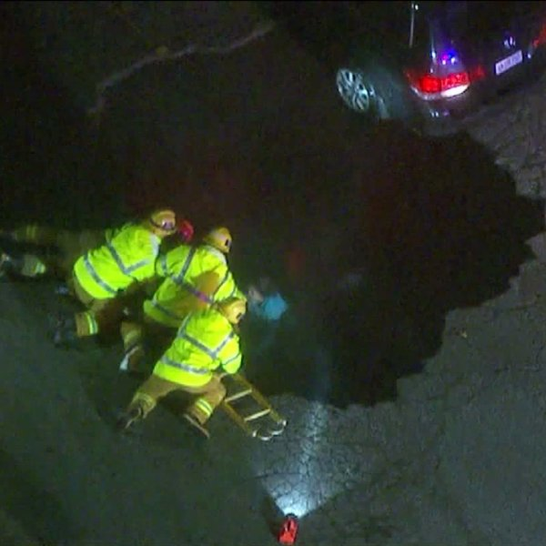 Authorities rescue a woman trapped in a sinkhole on Feb. 17, 2017. (Credit: KTLA)