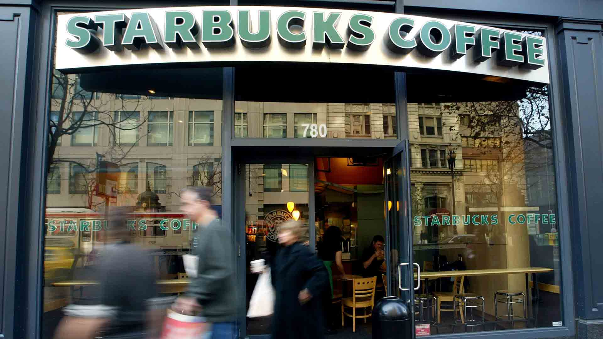 People walk out of a Starbucks coffee shop January 22, 2004 in San Francisco. (Credit: Justin Sullivan/Getty Images)