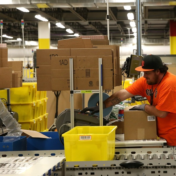 An Amazon.com worker packs orders at an Amazon fulfillment center on Jan. 20, 2015, in Tracy, California. (Credit: Justin Sullivan/Getty Images)