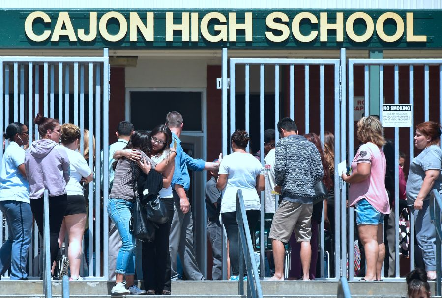 A student and her mother embrace one another upon leaving Cajon High School in San Bernardino on April 10, 2017. A shooting occurred at North Park Elementary School nearby in San Bernardino earlier in the day. (Credit: Frederic J. Brown/AFP/Getty Images)