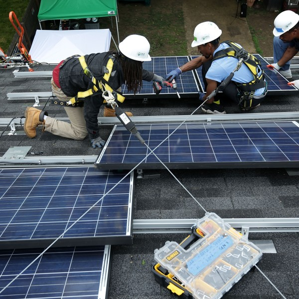 Workers put solar panels down during an installation on May 3, 2016, in Washington, DC. (Alex Wong / Getty Images)