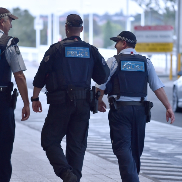 Police walk outside the international terminal as they patrol Sydney Airport on July 31, 2017. Four men accused of plotting to bring down a plane from Sydney planned to use poisonous gas or a crude bomb disguised as a meat mincer, reports said on July 31, with Australian officials calling preparations 'advanced'. (Credit: PETER PARKS/AFP/Getty Images)