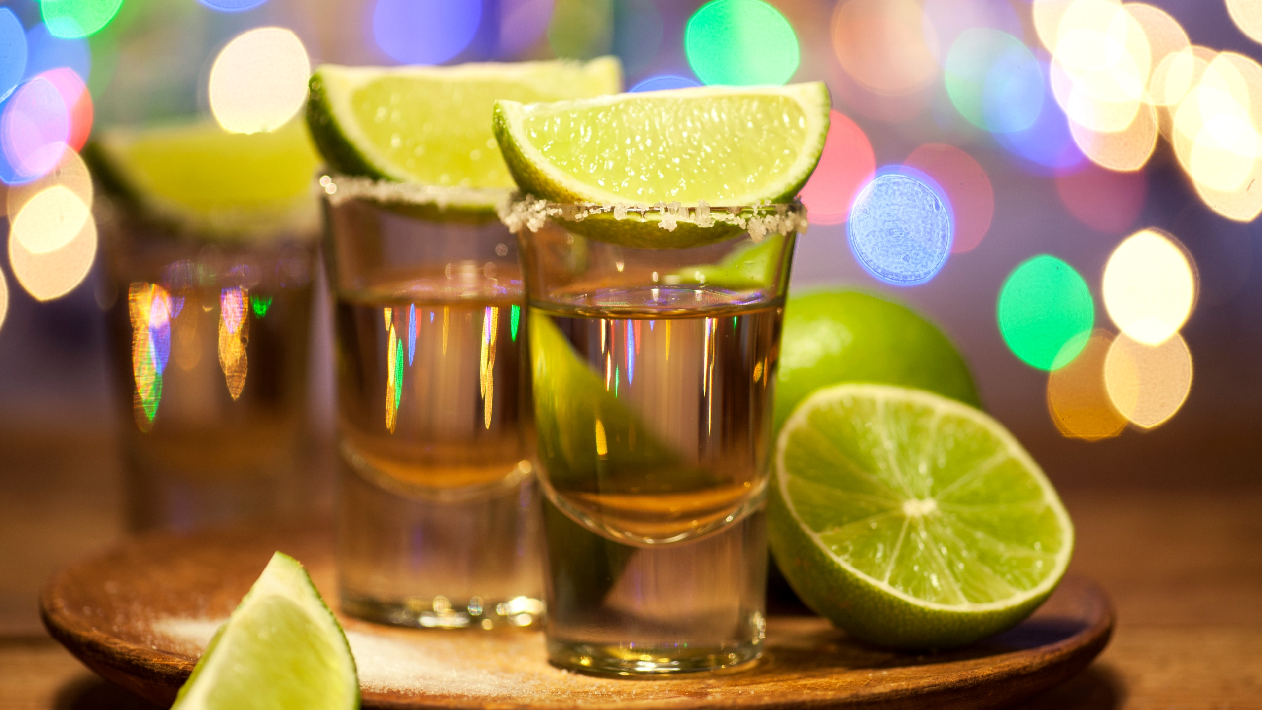 Gold tequila shots with lime fruits are seen in this file photo. (Credit: iStock / Getty Images Plus)