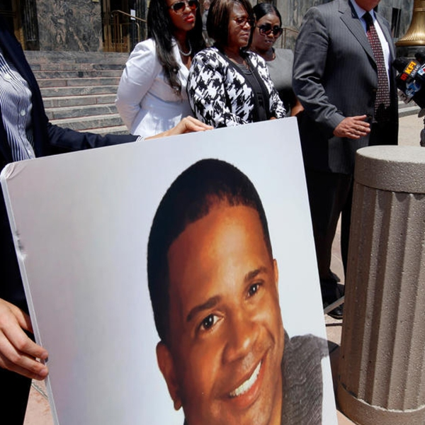 """A poster showing the face of Dennis """"Todd"""" Rogers, who was killed in a deputy-involved shooting in Ladera Heights in March, is held up at a press conference in Los Angeles. (Credit: Francine Orr / Los Angeles Times)"""