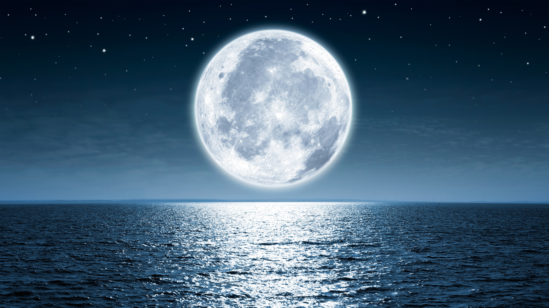 Full moon rising over empty ocean at night. (Credit: iStock / Getty Images Plus)