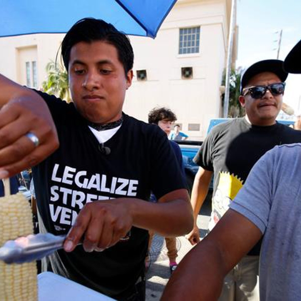 Benjamin Ramirez, left, with his father, Alex Ramirez, right, serving food from their cart during a rally in Hollywood. (Credit: Francine Orr / Los Angeles Times)
