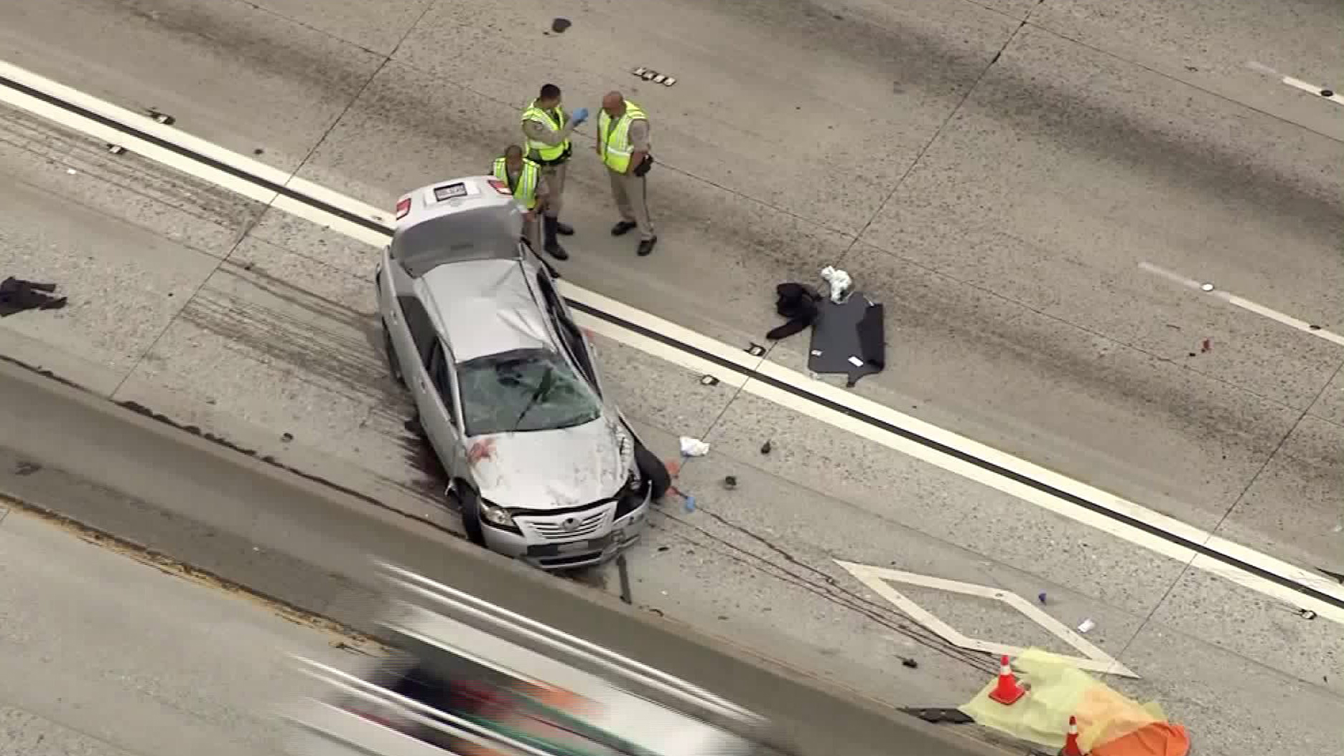 CHP officers inspect the scene of a fatal crash along the 605 Freeway in Norwalk where a Monterey Park police officer was killed on Aug. 14, 2017. (Credit: KTLA)