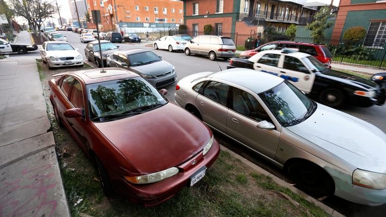 After a five-year hiatus, Los Angeles parking officers will resume ticketing drivers whose cars are parked on the grassy area between the sidewalk and the curb. The practice has proliferated in dense, central neighborhoods, including Koreatown and Westlake. (Credit: Al Seib / Los Angeles Times)