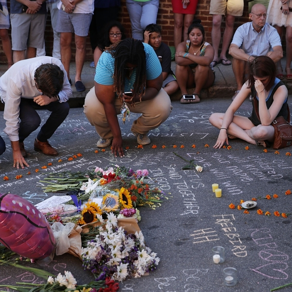 People pray and mourn at an informal memorial at the place where 32-year-old Heather Heyer was killed when a car plowed into a crowd of people protesting against the white supremacist Unite the Right rally Aug. 13, 2017, in Charlottesville, Virginia. (Credit: Chip Somodevilla/Getty Images)