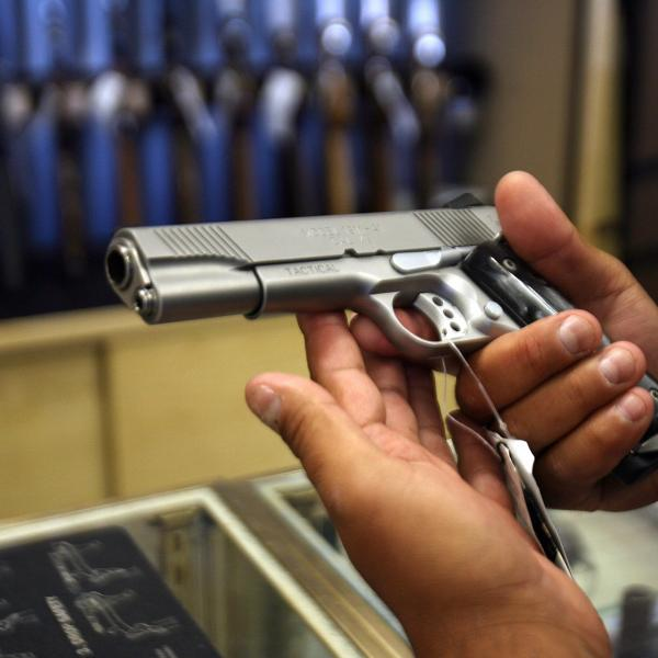 A man chooses a gun at the Gun Gallery in Glendale, California, April 18, 2007. (Credit: GABRIEL BOUYS/AFP/Getty Images)