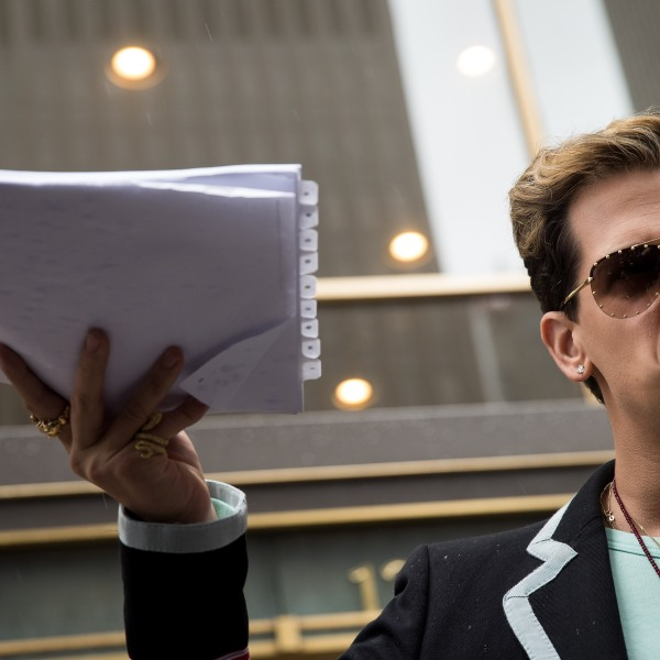 Milo Yiannopoulos holds up a copy of a legal complaint as he speaks outside the offices of Simon & Schuster publishing company, July 7, 2017, in New York City. (Credit: Drew Angerer / Getty Images)