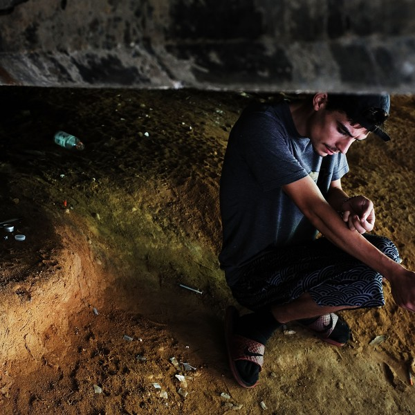 Mike, 22, a heroin addict who began using opiates when he was 13, pauses to shoot-up by a railway underpass in the Kensington section of Philadelphia, which has become a hub for heroin use, on July 31, 2017. (Credit: Spencer Platt / Getty Images)