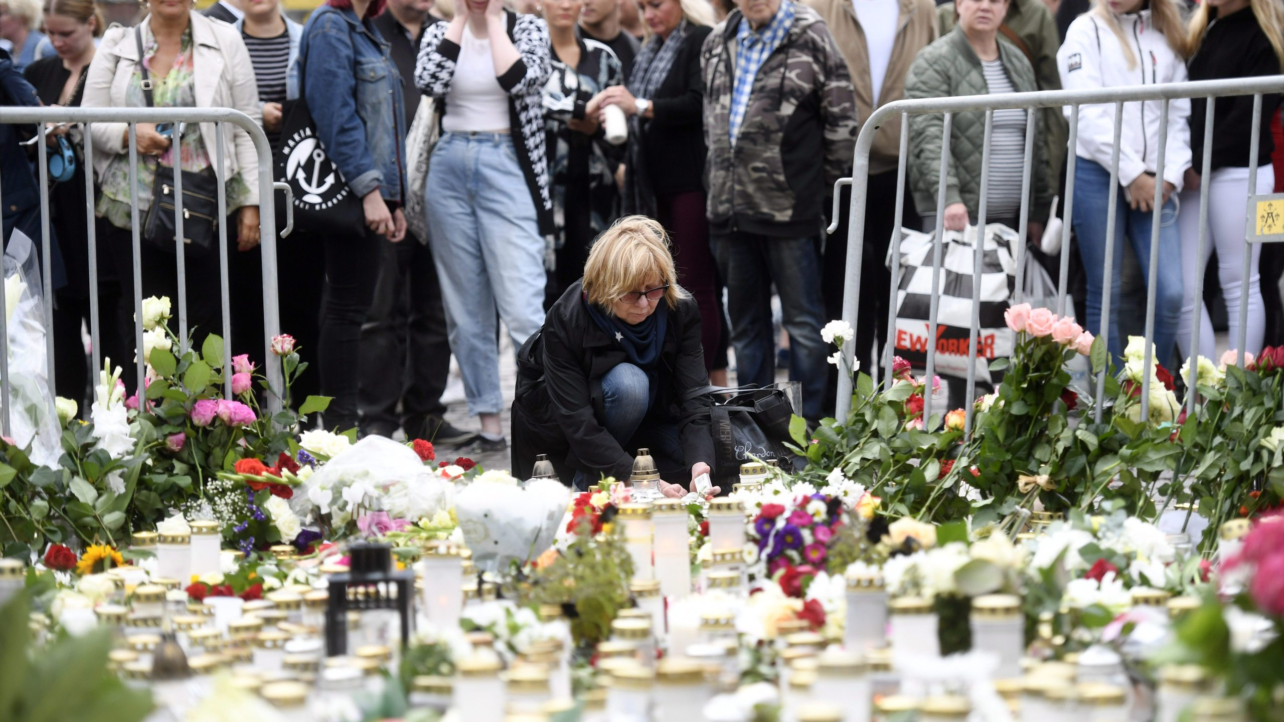 Candles and flowers are left at the makeshift memorial by well wishers for the victims of Friday's stabbings at the Turku Market Square in Finland on Aug. 19, 2017. (Credit: Vesa Moilanen / AFP / Getty Images)