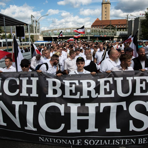 """Some 1,000 participants affiliated with Neo-Nazi and extreme right groups marched through the street of Berlin, Germany, in commemoration of 30 years to Rudolf Hess's death, on Aug. 19, 2017. This group is seen carrying a sign reading """"I regret nothing"""". (Credit: Omer Messinger / Getty Images)"""