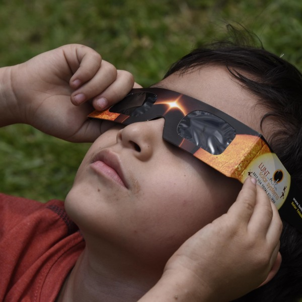People visiting to Miraflores Museum watch the partial solar eclipse through special glasses, in Guatemala City on August 21, 2017. (Credit: JOHAN ORDONEZ/AFP/Getty Images)