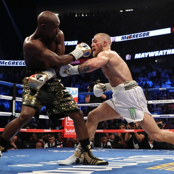 Conor McGregor throws a punch at Floyd Mayweather Jr. during their super welterweight boxing match on Aug. 26, 2017, at T-Mobile Arena in Las Vegas, Nevada. (Credit: Christian Petersen / Getty Images)