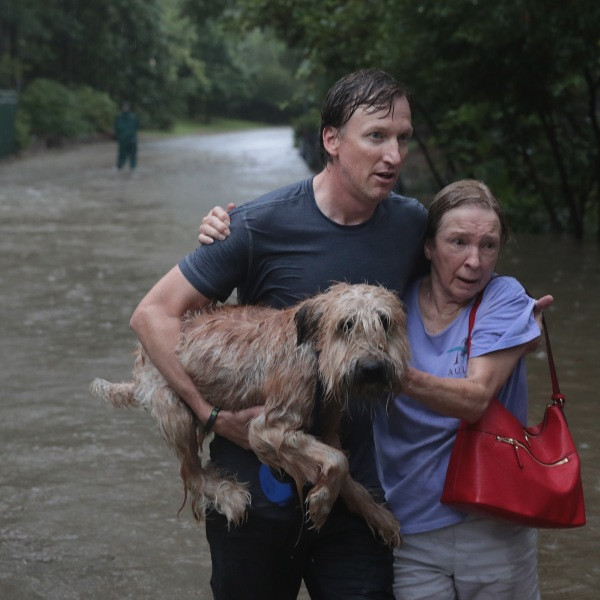 Andrew White, left, helps a neighbor down a street after rescuing her from her home in his boat in Houston after it was inundated with flooding from Hurricane Harvey on Aug. 27, 2017. (Credit: Scott Olson / Getty Images)