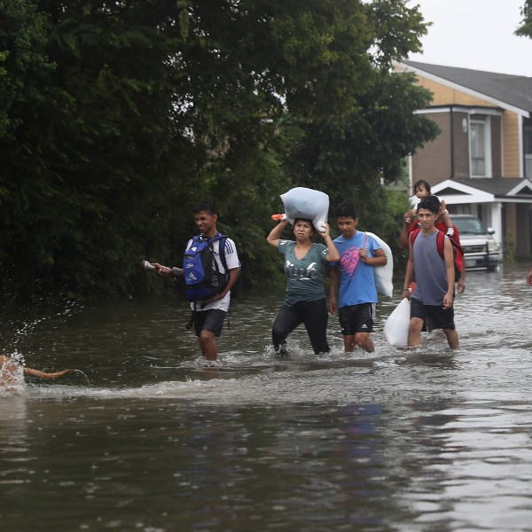 People walk down a flooded street as they evacuate their homes after the area was inundated with flooding from Hurricane Harvey on August 27, 2017 in Houston, Texas. (Credit: Joe Raedle/Getty Images)