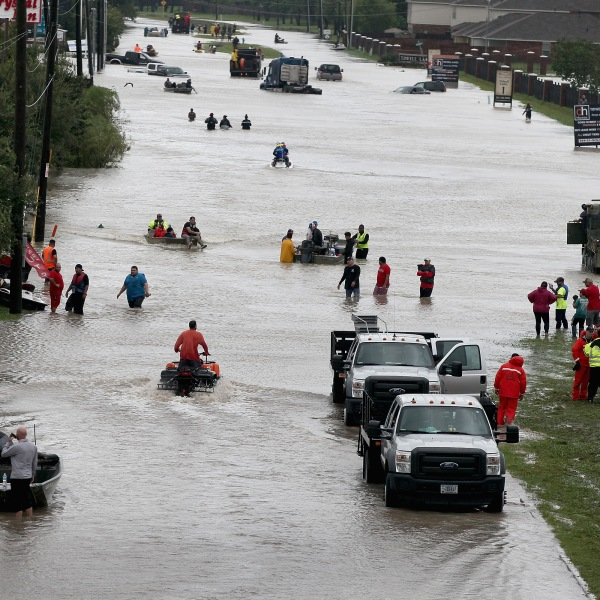People make their way out of a flooded neighborhood after it was inundated with rain water following Hurricane Harvey on August 29, 2017 in Houston, Texas. (Credit: Scott Olson/Getty Images)