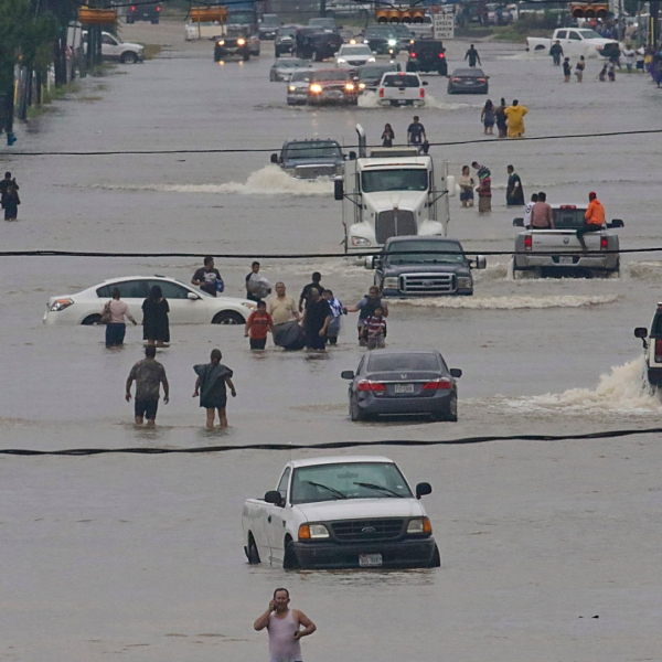 People walk through the flooded waters of Telephone Rd. in Houston on August 27, 2017 after Tropical Storm Harvey wreaks havoc on the region.(Credit: THOMAS B. SHEA/AFP/Getty Images)