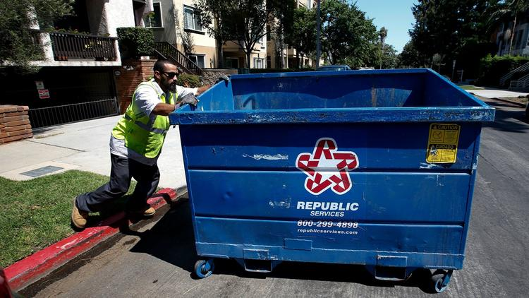 An employee with the trash hauler Athens Services moves a refuse bin outside a 14-unit condominium building in West Los Angeles. (Credit: Mel Melcon / Los Angeles Times)