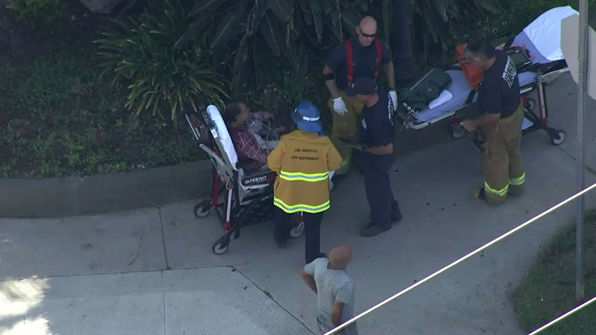 L.A. firefighters help a person hurt in a fire at an apartment building in Van Nuys on Aug. 9, 2017. (Credit: KTLA)